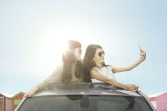 Young women taking selfie photo on car sunroof. Two young women taking selfie photo with smartphone on a car sunroof near the cottage Royalty Free Stock Photography
