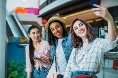 Young women taking selfie in shopping mall, young girls shopping concept. Smiling young women taking selfie in shopping mall, young girls shopping concept Stock Photos