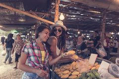 Young Women Talking While Buy Exotic Fruits On Tropical Market Happy Smiling Girld Tourists In Asian Traditional Bazaar. Young Women Talking While Buy Exotic Stock Photography