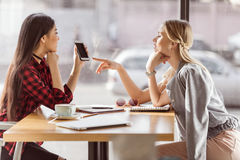 Young women talking while having business lunch meeting in cafe