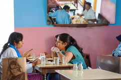 Young women talking and having dinner in popular indian cafe with colorful interior Royalty Free Stock Photography