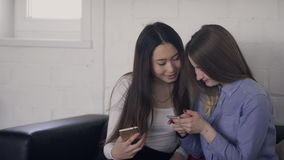Young women talking holding phones in hands indoors. They look with interest at screen of silvery smartphone stock footage