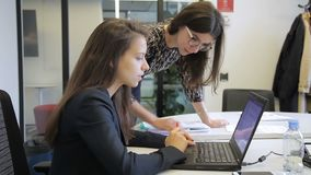 Young women talking while looking at laptop in modern office. Two employees look attentively at black p screen and discuss actively, information they see stock footage
