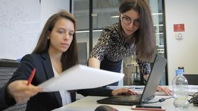Young women are talking, looking at PC screen in modern office. Brunette demonstrates to colleague information on display of black laptop, pointing with pen stock footage