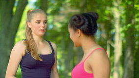 Young women talking in park. Two beautiful girls talking outdoor. Fitness woman talking outdoor. Two girlfriends having fun talking. Multiracial friends stock video