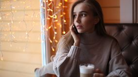 Young women talking on the phone in the cafe, drinking coffee. Bokeh background. Winter stock footage