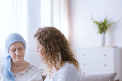 Woman talking with sick mother. Young women talking with sick mother battling with malignant cancer Royalty Free Stock Image