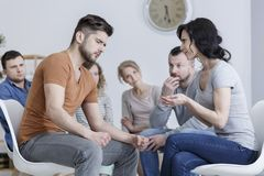 Anger management classes. Young women talking to tense men during anger management class royalty free stock photography