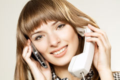 Young women talking on two cellular phones Royalty Free Stock Photos