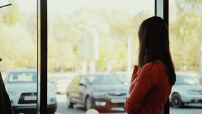 A young women talks on the phone near the window in cafe. stock footage