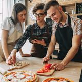 Young woman teach her friends how to cook food. People cooking p. Young women teach her friends how to cook food. People cooking pizza at kitchen together Royalty Free Stock Photos