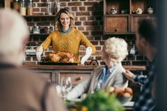 Young woman with thanksgiving turkey for holiday dinner. Young women with thanksgiving turkey for holiday dinner with family royalty free stock photo