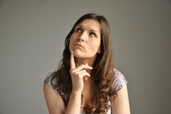 A young women thinks about something important. A young woman thins about something important with her finger on chin Royalty Free Stock Image