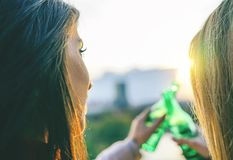 Young women toasting beer on a sunset - Happy friends drinking and cheering beers in a park outdoor admiring the beautiful view royalty free stock photo