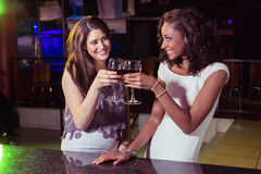 Young women toasting wine glasses at bar counter Stock Image
