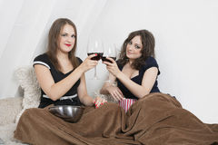 Young women toasting with wine glasses in bed Stock Photo