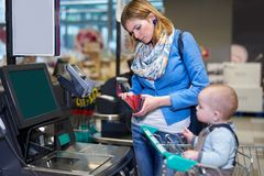 Young woman with baby paying with self checkout. Young women with toddler staying in front of self checkout machine and looking with serious face into her purse Royalty Free Stock Images