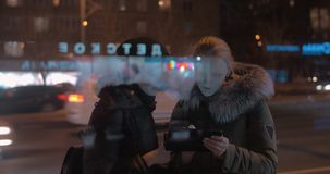 Young women with touch pad in evening city. Two women friends using digital tablet in the evening city. Road with intense car traffic in background. View through stock footage
