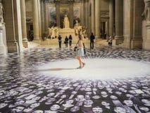 Young women tourist walks through JR display in Paris Pantheon Stock Image