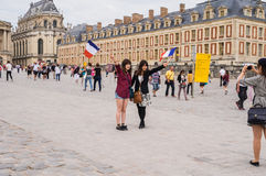 Young women tourists pose for friend's camera at Versailles Stock Images