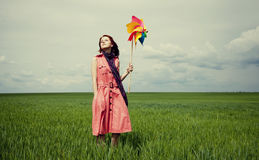 Young women with toy wind turbine at green wheat field. Royalty Free Stock Image