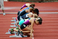 Young women track athletes in starting block at the starting line. An illustration of young women track sprinter ready to go at an track and field event Stock Photo