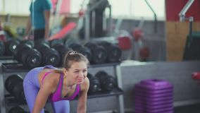 Young women training in the gym: woman smiles and tilts makes the pole stock footage