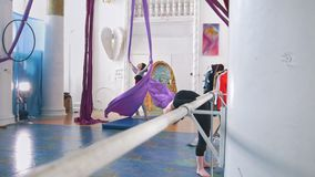 Young women trains air gymnastic in a studio. Telephoto shot stock video