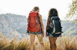Young women traveling together into mountains stock photo