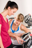 Young women on treadmill giving instructions royalty free stock image
