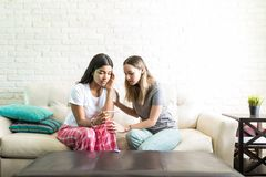 Woman Comforting Friend After She Got Positive Pregnancy Test. Young women trying to comfort best friend after she got a positive pregnancy test at home royalty free stock image