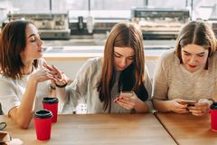 Woman trying to speak to friends who ignore her. Young women trying to speak to her inattentive gadget addicted friends. Women engrossed in typing on smart phone Stock Photo