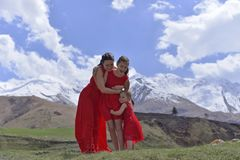 A young woman with two daughters in red dresses resting in the snow-capped mountains in the spring. A young women with two daughters in red dresses resting in royalty free stock photos