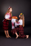 Young women in ukrainian clothes, with garland and round loaf Royalty Free Stock Photos