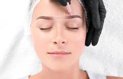 Woman undergoing eyebrow correction procedure in salon, top view. Young women undergoing eyebrow correction procedure in salon, top view royalty free stock photography
