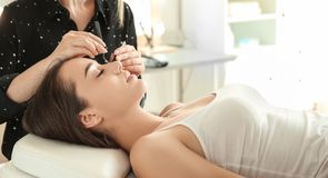 Young woman undergoing eyelash extensions procedure. Young women undergoing eyelash extensions procedure in salon stock photography