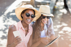 Young women using digital tablet and mobile phone. Young women having fun while using digital tablet and mobile phone Stock Photography