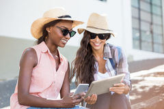 Young women using digital tablet and mobile phone. Young women in sunglasses using digital tablet and mobile phone Stock Image