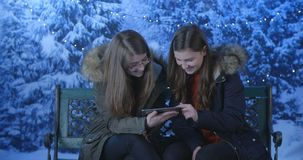 Young women using the digital tablet in park. In winter stock footage