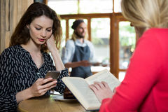 Young women using phone and reading book in coffee shop Stock Photo