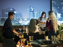 Young women using a smartphone at a dinner night having no inter. Action with friends addiction concept stock photography