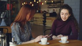 Young women are using smartphone, talking and doing high five while drinking tea in cafe in lunchtime. Communication. Young attractive women are using smartphone stock video