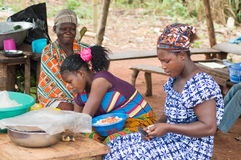 Young women vendors. Akoupé, ivory coast-August 20, 2015: three young women sell food, one woman is very busy chopping onions and tomatoes to flavor dishes Royalty Free Stock Photography