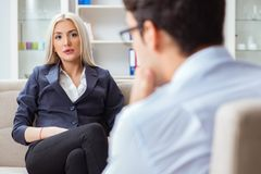 The young woman visiting psychiatrist man doctor for consultation. Young women visiting psychiatrist men doctor for consultation Royalty Free Stock Images