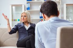 The young woman visiting psychiatrist man doctor for consultation. Young women visiting psychiatrist men doctor for consultation Royalty Free Stock Photos