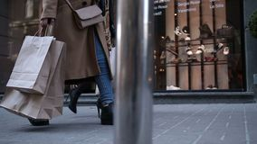 Young women walking with bags after shopping. Shopping therapy. Closeup of elegant slim females legs walking down the street and carrying shopping bags after stock footage