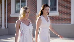 Young women walking down street in summer sunlight and chatting. Two charming girls in white talking while having walk at street stock footage