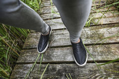 Young women walking feet on a wooden floor, summer time in Polan Stock Photo
