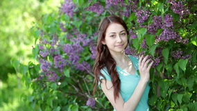 Young women walking outside in a park lilac tree.  stock video