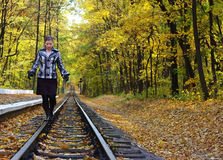 Young women walking on rails. In a autumn park Royalty Free Stock Images